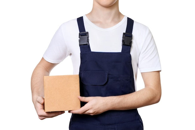 Молодой человек в синем комбинезоне и белой футболке, держа в руках картонную коробку, изолированную на белом фоне. концепция доставки.