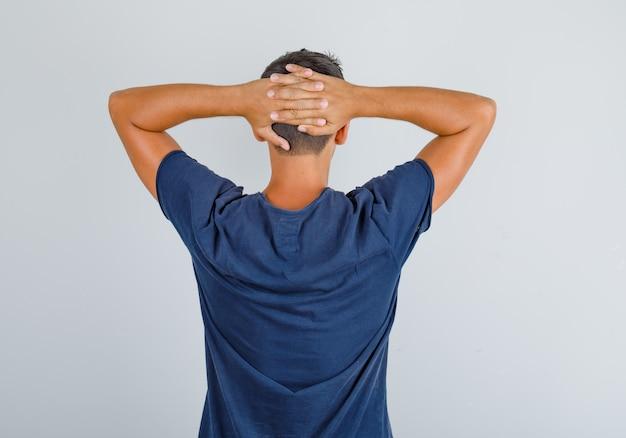 Молодой человек в темно-синей футболке, скрестив руки за головой и выглядел расслабленным, вид сзади.