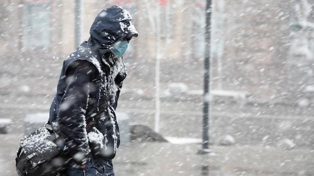 Covid-19マスクから身を守るために暗い服と医療の若い男が雪に覆われた通りを移動します。