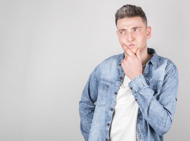 デニムシャツを着た若い男が物事を考える