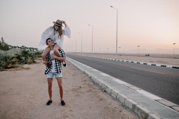 高速道路の近くに立っている肩に優雅なガールフレンドを抱えているデニムショートパンツの若い男。ボーイフレンドと一緒に時間を過ごし、屋外のデートを楽しんでヴィンテージの白いブラウスで愛らしい女性