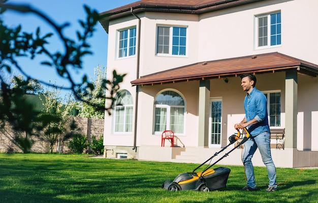 デニムの若い男は裏庭の大きなカントリーハウスの近くで電気芝刈り機を使用して芝刈り機を着用します