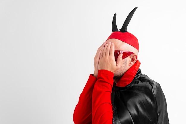 仮面舞踏会の服と赤い帽子をかぶった絶望の若い男は、白い背景の手で顔を覆っている黒い角があります。