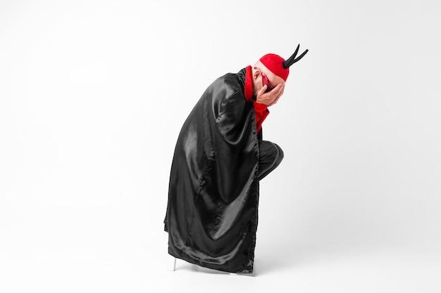 仮面舞踏会の服と手で顔を覆っている黒い角の赤い帽子で絶望している若い男