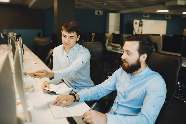 Молодой человек в элегантной рубашке показывает своему коллеге, сидящему рядом что-то за экраном компьютера, оба обсуждают это, улыбаясь
