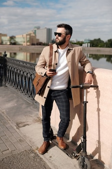 배경에 도시 환경과 강변에 의해 다리에 서 우아한 세련된 캐주얼웨어와 선글라스에 젊은 남자