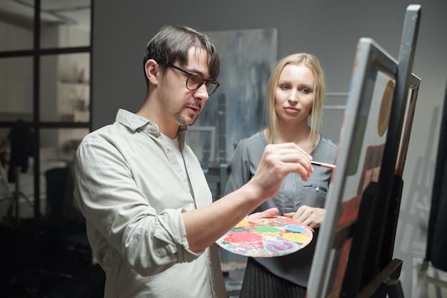 眼鏡の若い男と芸術のスタジオで新しい絵画の作業中にイーゼルの前に立っている金髪の女性