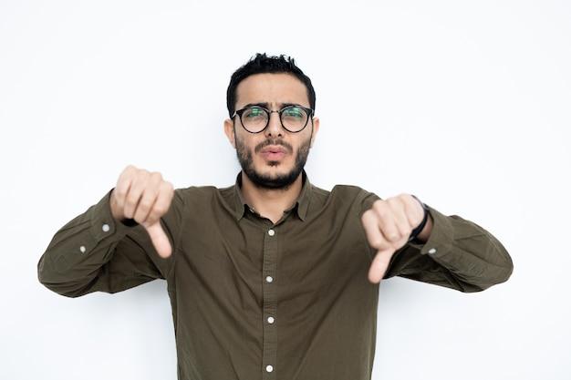 Молодой человек в очках и повседневной одежде демонстрирует жест неприязни изолированно