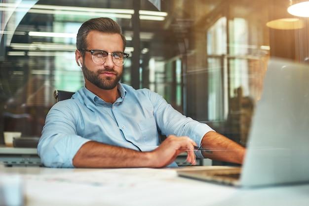 Молодой человек в очках и формальной одежде работает с ноутбуком, сидя в современном офисе