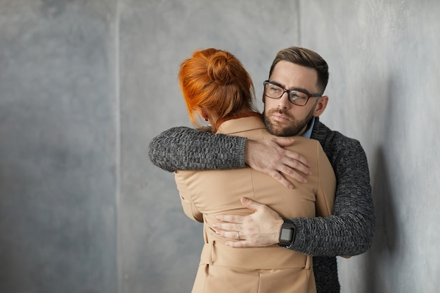 彼らが灰色の壁に立っている間、女性を抱きしめ、彼女をサポートする眼鏡の若い男