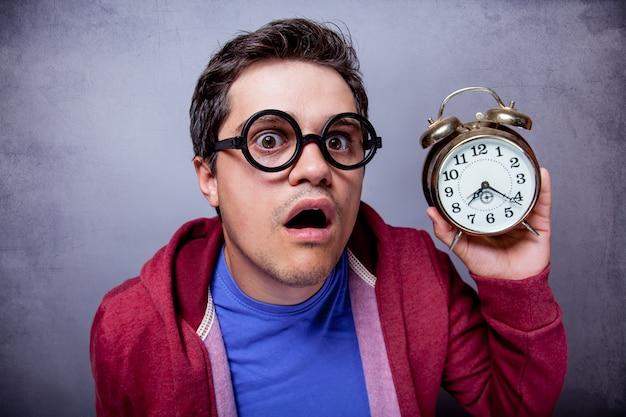 Молодой человек в очках с металлическим будильником на сером