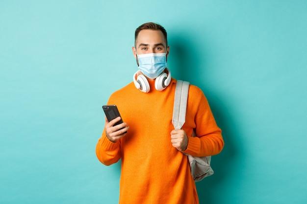 휴대 전화를 사용하여 얼굴 마스크를 쓴 젊은 남자, 배낭을 들고 밝은 파란색 배경에 서 있습니다. 복사 공간