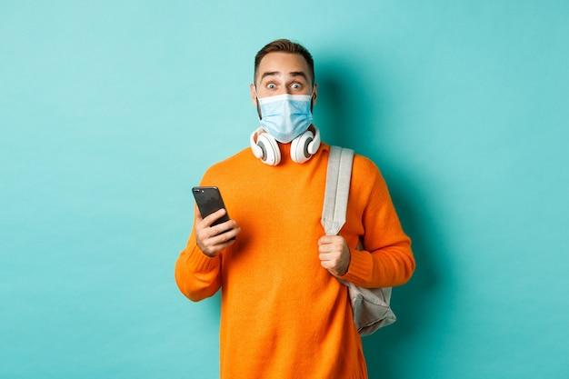 携帯電話を使用して、バックパックを保持し、カメラに感銘を受けて見つめ、水色の背景に立って、フェイスマスクの若い男。