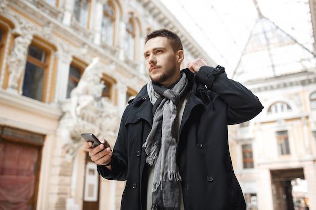 秋の服の若い男が会議開催電話に向かっています。