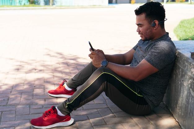 운동하는 동안 휴대 전화로 음악을 듣고 피트니스 옷을 입은 젊은 남자. 음악을 듣고 피트 니스 남자의 초상화입니다.
