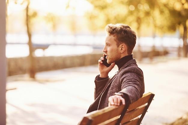 Молодой человек в формальной одежде находится в осеннем парке в солнечный день у звонка.
