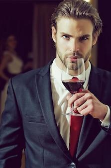 Молодой человек в формальном наряде с красным галстуком держит бокал для вина рядом с женщиной.