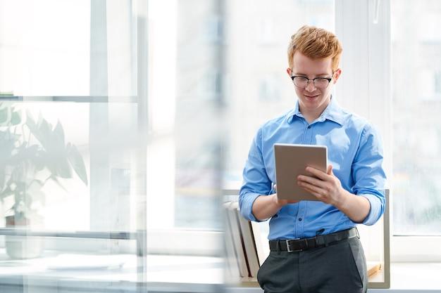 オフィスでオンライン情報を見ながらタブレットでスクロールする正装の若い男
