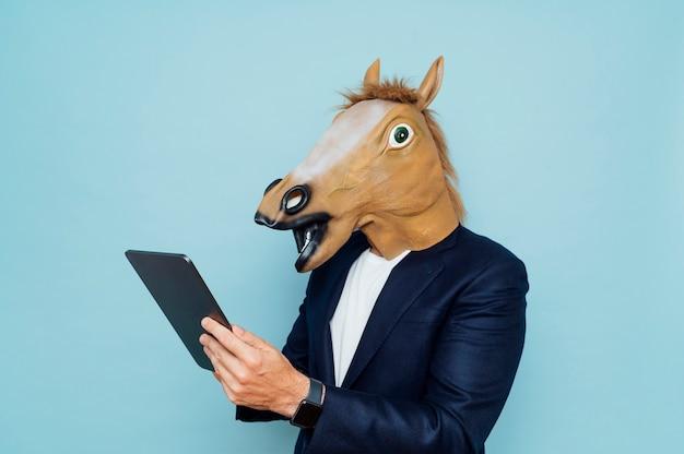 面白い馬マスクの若い男は、ポータブルタブレットで動作します。