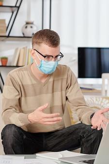 Covid-19 전염병으로 인해 집에서 일할 때 안경 및 의료 마스크의 젊은 남자가 동료들과 화상 회의를 가졌습니다.