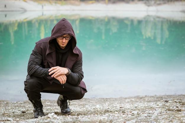 가을 오후 청록색 호수 배경에 후드가 달린 안경과 조끼를 입은 청년...