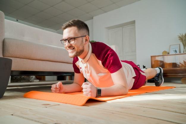 自宅でマットの上で運動をしている眼鏡の若い男