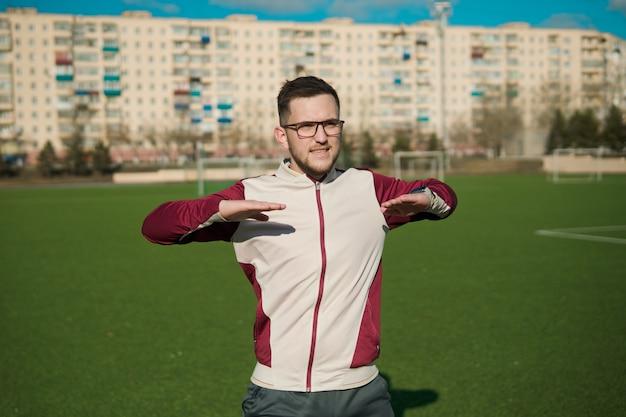 Молодой человек в очках, растягиваясь на стадионе