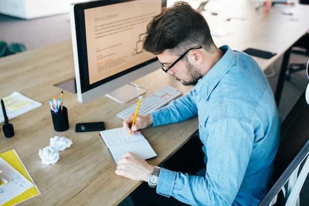 Молодой человек в очках работает на своем рабочем месте в офисе. он носит синюю рубашку. он пишет в блокноте. вид сверху.
