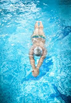 Молодой человек в очках плавает под водой в бассейне