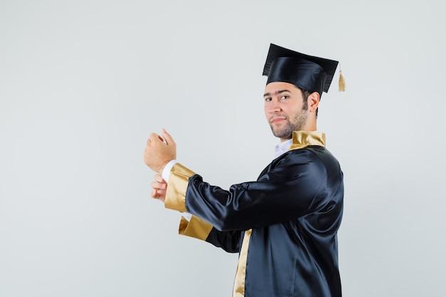Молодой человек в форме выпускника застегивает рукав рубашки и выглядит гордым.