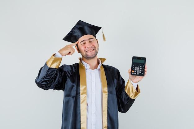 사원에 손가락으로 계산기를 들고 기쁜, 전면보기를 찾고 대학원 제복을 입은 젊은 남자.