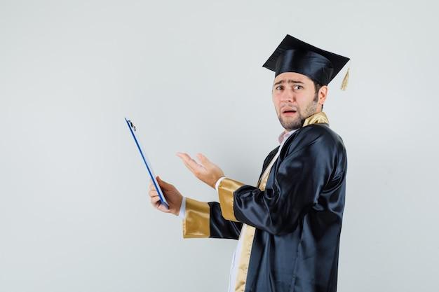 クリップボードを保持し、問題を抱えているように見える大学院の制服を着た若い男。