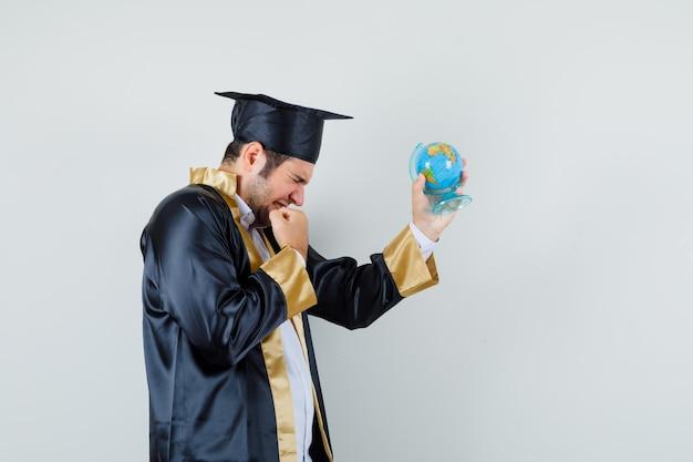 대학원 제복을 입은 젊은 남자가 학교 지구본을 들고 행복을 찾고 있습니다.