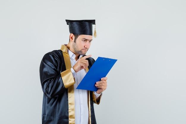 クリップボード、正面図のメモを見ている大学院の制服を着た若い男。
