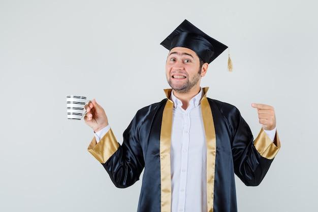 一杯のコーヒーを指して、陽気に見える卒業式の制服を着た若い男、正面図。