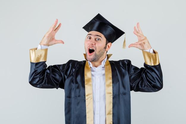 대학원 제복을 입은 젊은 남자가 손을 올리고 놀란 모습을보고 있습니다.