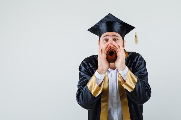 대학원 제복을 입은 젊은 남자가 외치거나 비밀을 말하고 불안, 전면보기를 찾고 있습니다.