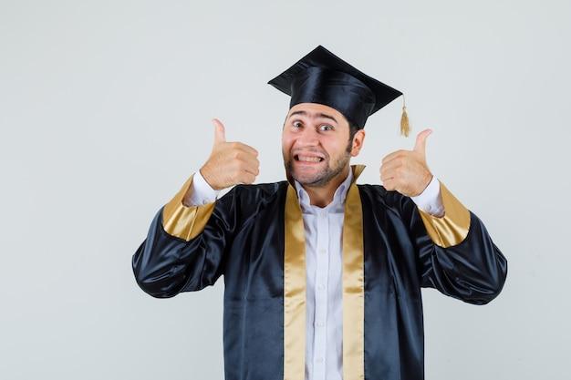 卒業式の制服を着た若い男が二重の親指を立てて陽気に見える、正面図。