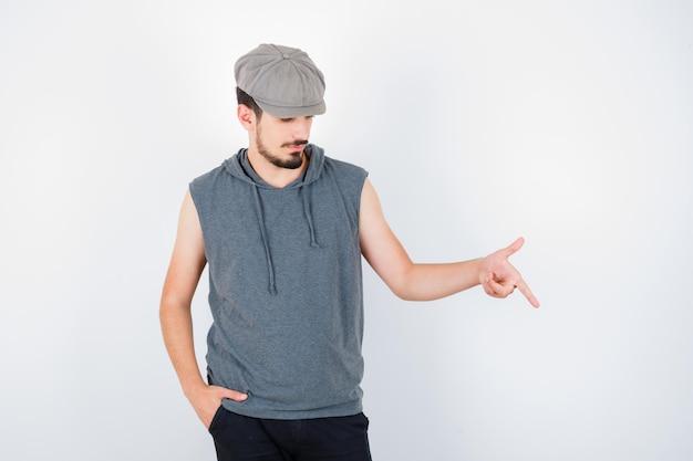 灰色のtシャツとキャップの若い男が人差し指で下を向いてポケットに手をつないで真剣に見える