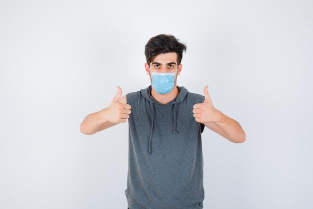 灰色のtシャツを着た若い男が、二重の親指を立てて真剣に見えながらマスクを着用