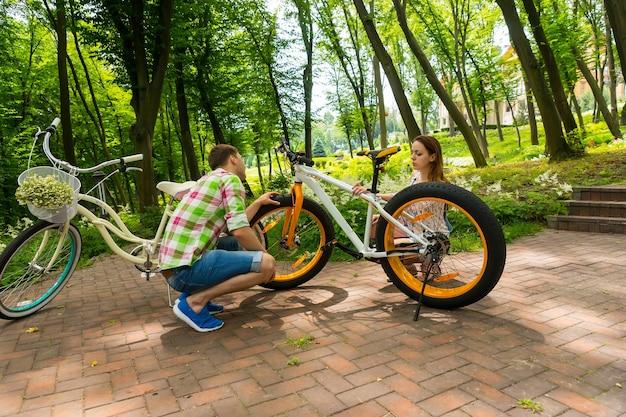 녹색과 빨간색 체크무늬 셔츠를 입은 젊은 남자와 그의 여자친구가 공원에서 자전거를 탄 후 자전거를 고치려고 한다