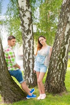 녹색과 빨간색 체크무늬 셔츠를 입은 청년과 분수와 다른 나무가 있는 공원에서 나무에 기대어 카메라를 바라보는 여성