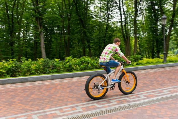 公園の歩道で自転車に乗って緑と赤の格子縞のシャツを着た若い男