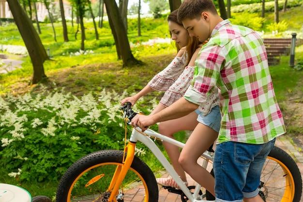 녹색과 빨간색 체크무늬 셔츠를 입은 청년은 공원이나 숲에서 자전거를 타는 여자친구를 가르친다