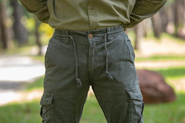 Молодой человек в зеленых штанах, стоящий в парке
