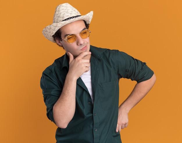 녹색 셔츠와 안경을 쓰고 여름 모자에 젊은 남자가 옆으로 오렌지 벽 위에 서 의아해