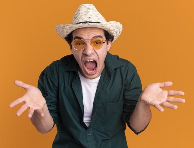 緑のシャツと夏の帽子をかぶった若い男がオレンジ色の壁の上に立って手を上げて野生に向かって叫んで正面を見て眼鏡をかけている