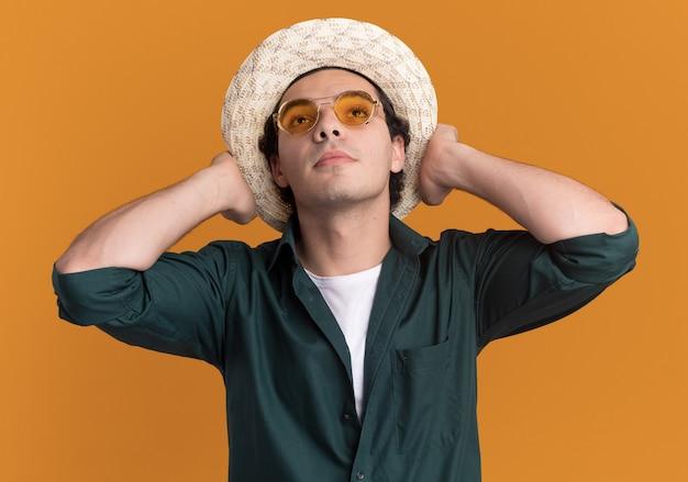 오렌지 벽 위에 서있는 똑똑한 얼굴에 자신감이 표정으로 올려다 보는 안경을 쓰고 녹색 셔츠와 여름 모자에있는 젊은 남자
