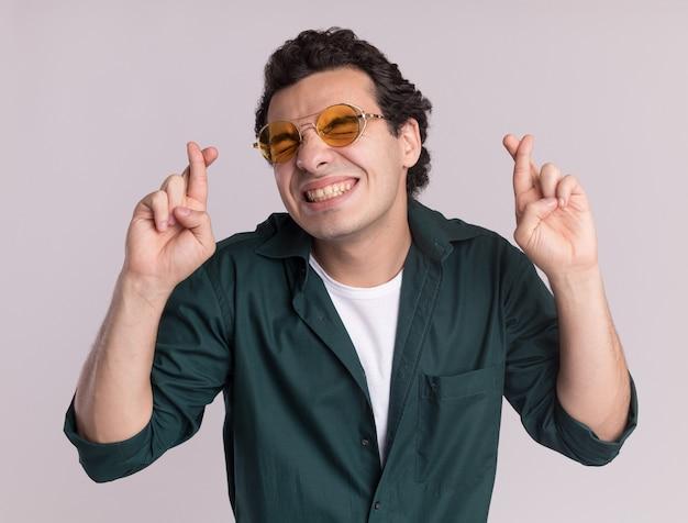 안경을 쓰고 녹색 셔츠에 젊은 남자가 흰 벽 위에 서있는 닫힌 눈을 가진 미친 행복 횡단 손가락