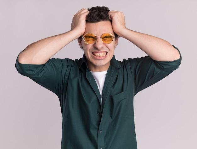 眼鏡をかけている緑のシャツを着た若い男は、白い壁の上に立っている彼の髪を引っ張って野生になり狂っています
